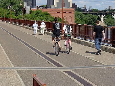 A Pair of Unicyclists on the Stone Arch Bridge