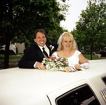 Couple standing up through limo sunroof